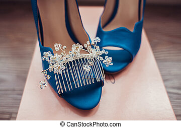 Bridal morning details composition: wedding rings and blue leather shoes.