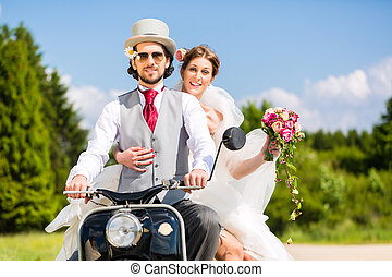 Bridal pair driving motor scooter wearing gown and suit -...