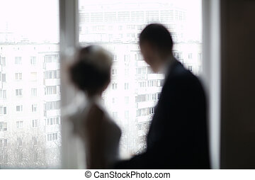 Bridal pair looking out the window - Bride and groom out of...