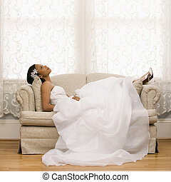 African-American bride lying on love seat.