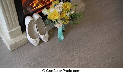 Bridal shoes and bouquet near fireplace