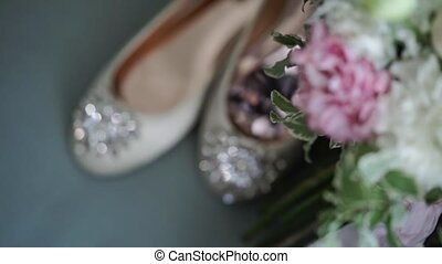 Bridal shoes and bouquet on blue background