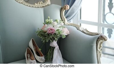 Bridal shoes and bouquet on blue sofa