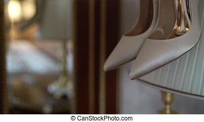 Bridal shoes at lamp in bedroom mirror reflection