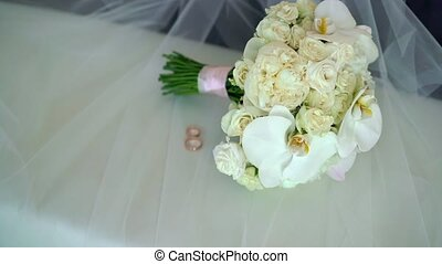 Bridal wedding bouquet of white roses on veil and two...
