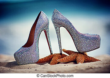 Bridal wedding shoes with diamante on starfish over beach ...