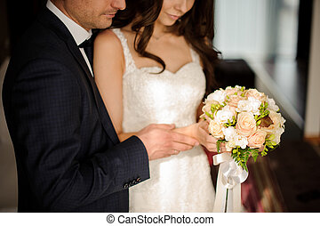 bride and bridegroom looking together at the bouquet of...