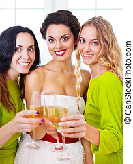 Bride and bridemaids holding wedding glass with champagne