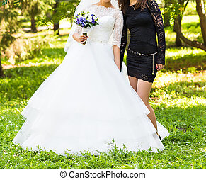 bride and bridesmaid outdoors
