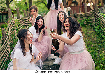 Bride and bridesmaids opening bottle of champagne, sitting on steps