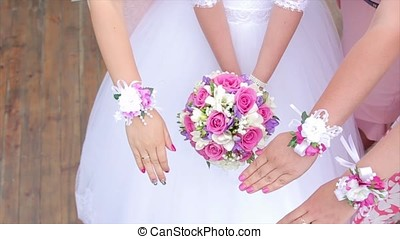 Bride and bridesmaids show bouquets of flowers. Bride and her girlfriends stand side by side and show the bouquets in their hands. Bride with flowers in hand outdoors. The bride is nervous before the wedding. Bride holding a perfume. nice wedding bouquet in bride's hand. Bride is holding beautiful bright wedding bouquet. the bride holding wedding bouquet of pink and white roses. Woman