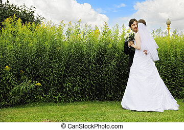 Bride and groom against grass
