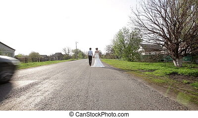 bride and groom are on the road
