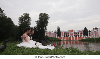 Bride and groom are sitting on grass in the park.