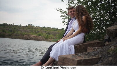 bride and groom are sitting on the shore of the lake