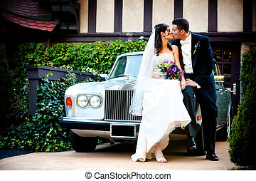 Bride and groom at a wedding kissing on a fancy car
