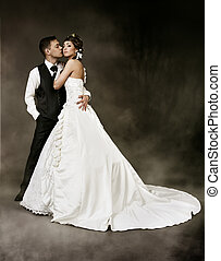 Bride and groom at dark mysterious background. Wedding couple fashion shoot.