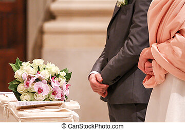 bride and groom at the altar with bouquet of flowers