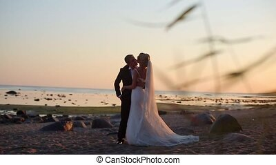 Bride and groom at the beach at sunset