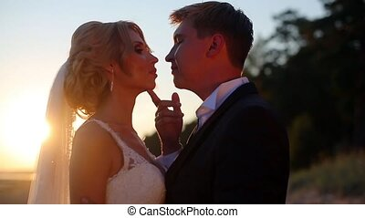 Bride and groom at the beach - Bride and groom kissing at...