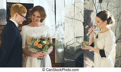 Bride and groom at wedding ceremony exchange ring each other while registrar talking