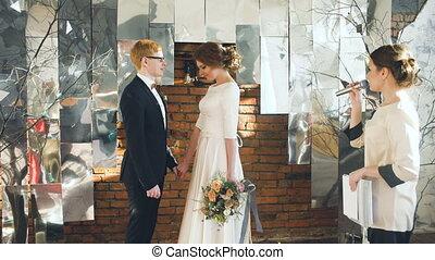Bride and groom at wedding ceremony kiss after registrar speech. Celebration indoors