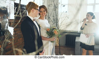 Bride and groom at wedding ceremony listen to registrar speech