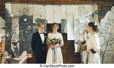 Bride and groom at wedding ceremony talk oath to each other while registrar speech