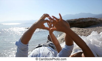 Bride and groom by the sea on their wedding day make a heart out of fingers