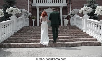 bride and groom climb the stairs to a beautiful house, rear view