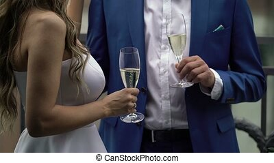 Bride and groom clink glasses with champagne