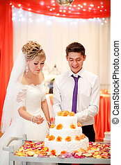 Bride and groom cut the cake at a banquet with orange flowers in decoration.