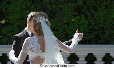 Bride and groom dance outdoor in sunny day