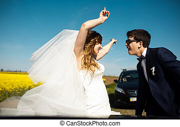 Bride and groom dance standing on the road in a sunny day