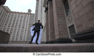 Bride and groom dancing on the background of the building
