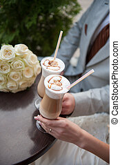 bride and groom drink latte with painted hearts