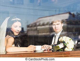 Bride and groom drinking coffee in cafe