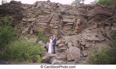 bride and groom embrace on a wedding walk in the background of the mountain