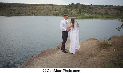 bride and groom embrace on a wedding walk against the lake