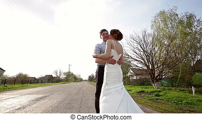 Bride and groom embrace on the road
