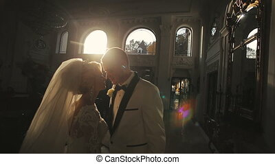 Bride and groom embraces in palace on sunset