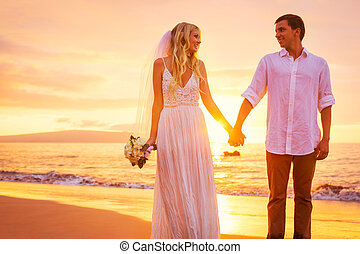 Bride and Groom, Enjoying Amazing Sunset on a Beautiful Tropical Beach, Romantic Married Couple Holding Hands, Just Married