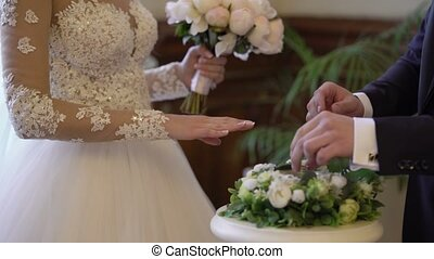 Bride and groom exchange wedding rings on ceremony
