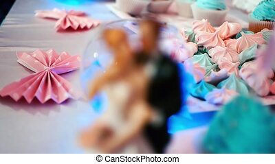 Bride and groom figures on wedding cake on blinking background