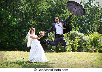 Bride and groom flying on umbrella