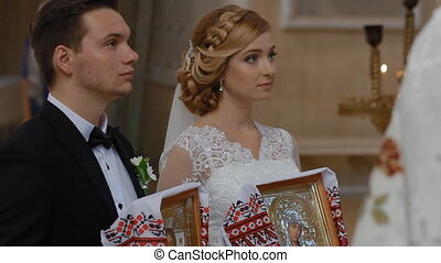 Bride and groom get married in church. They listen to cleric...