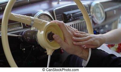 Bride and groom hands on steering wheel of retro car shot