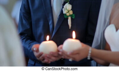 bride and groom hold candles at the altar