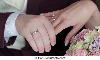 bride and groom hold hands and show their wedding rings