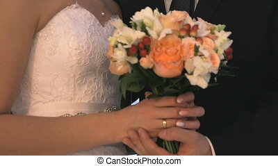 Bride and groom hold hands indoors